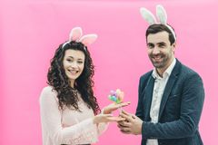 Young happy family on a pink background. At the same time on the head there is a rabbit`s ears. During this look in the. Camera and hold in their hands royalty free stock photos