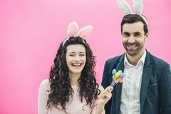 Young happy family on a pink background. At the same time on the head there is a rabbit`s ears. During this look in the. Camera, the wife holds decorative stock photo