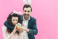 Young happy family on a pink background. At the same time on the head there is a rabbit`s ears. During this man holding. Young happy family on a pink background royalty free stock photo