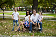 Young happy family portrait on background of the autumn park Stock Photo