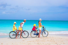 Young happy family riding bicycles duting beach Stock Images