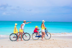 Young happy family riding bicycles duting beach Royalty Free Stock Photo