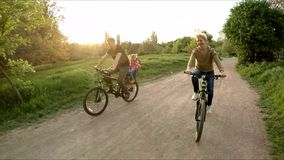 Young Happy Family Riding Bicycles In Green Park stock video footage