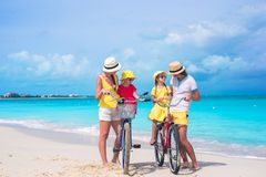 Young happy family riding bicycles on tropical Stock Image