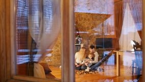Young happy family sitting on the floor in cozy house. View from the window stock footage
