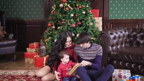 A young and happy family sitting near a festively decorated Christmas tree and start to read a book of their young son stock video