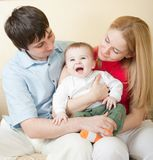 Young happy family sitting on sofa Royalty Free Stock Photo