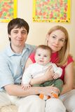 Young happy family sitting on sofa Royalty Free Stock Photography