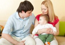 Young happy family sitting on sofa Royalty Free Stock Images