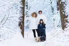 Young happy family with son walking in snowy park. Young happy family with a little son walking and playing in a snowy winter park Royalty Free Stock Images