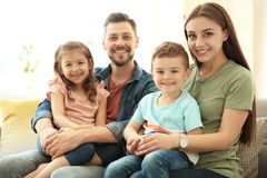 Young happy family with children at home. Young happy family spending time together with children at home royalty free stock images