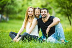 Young happy family in summer park. Father and mother spend time in summer park with their daughter. Stock Photography