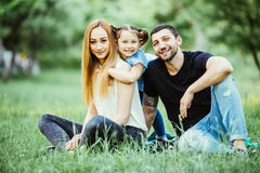 Young happy family in summer park. Father and mother spend time in summer park with their daughter while she hug them. Stock Images