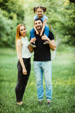Young happy family of three having fun together outdoor. Pretty little daughter on her father back. Father carrying daughter piggy Royalty Free Stock Photography
