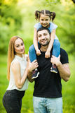Young happy family of three having fun together outdoor. Pretty little daughter on her father back. Father carrying daughter piggy Royalty Free Stock Photo