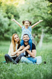 Young happy family of three having fun together outdoor. Pretty little daughter on her father back with happy raised hands. Parent Royalty Free Stock Photography