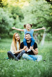 Young happy family of three having fun together outdoor. Pretty little daughter on her father back with happy raised hands. Parent Stock Photos