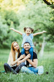 Young happy family of three having fun together outdoor. Pretty little daughter on her father piggyback smiling and have fun. Stock Photo