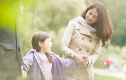 Young happy family of three walking outdoor. Young family of three enjoys walking in park. Pretty daughter holding hands of her parents. Focus on little happy Royalty Free Stock Photos