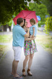 Young happy family under umbrella Stock Images