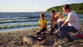 Young family fry marshmallow on skewers on fire near sea on a windy summer day stock video