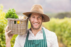 Young happy farmer holding a basket of vegetables Royalty Free Stock Photo