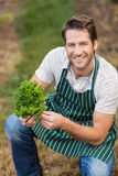 Young happy farmer looking at camera while holding vegetable Stock Image