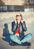 Young happy fashion beautiful girl in leather jacket, hat and su Stock Photos