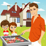 Young Happy Father Barbecuing Meat On The Grill Royalty Free Stock Photography