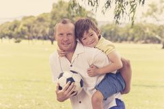 Young happy father carrying on his back excited 7 or 8 years old son playing together soccer football on city park garden posing s. Weet and loving holding the stock image