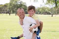Young happy father carrying on his back excited 7 or 8 years old son playing together soccer football on city park garden posing s. Weet and loving holding the royalty free stock images