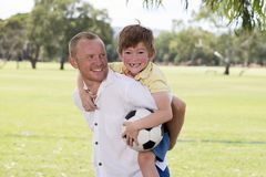 Young happy father carrying on his back excited 7 or 8 years old son playing together soccer football on city park garden posing s. Weet and loving holding the Royalty Free Stock Photography