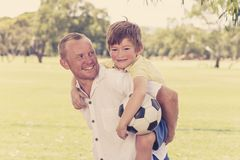 Young happy father carrying on his back excited 7 or 8 years old son playing together soccer football on city park garden posing s. Weet and loving holding the Royalty Free Stock Photo