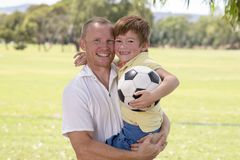 Young happy father carrying on his back excited 7 or 8 years old son playing together soccer football on city park garden posing s. Weet and loving holding the Royalty Free Stock Image