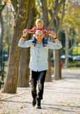 Young happy father carrying little son on shoulders having fun royalty free stock image
