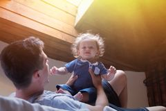 Young happy father and child play in a bed stock images