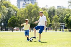 Young happy father and excited little 7 or 8 years old son playing together soccer football on city park garden running on grass k. Young happy father and Royalty Free Stock Image