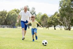 Young happy father and excited little 7 or 8 years old son playing together soccer football on city park garden running on grass k. Young happy father and Royalty Free Stock Photography
