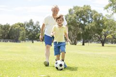 Young happy father and excited little 7 or 8 years old son playing together soccer football on city park garden running on grass k. Young happy father and Stock Images