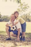 Young happy father and excited 7 or 8 years old son playing together soccer football on city park garden posing sweet and loving h. Olding the ball in dad and stock photo