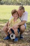 Young happy father and excited 7 or 8 years old son playing together soccer football on city park garden posing sweet and loving h. Olding the ball in dad and Royalty Free Stock Photo