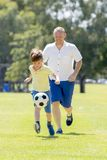Young happy father and excited little 7 or 8 years old son playing together soccer football on city park garden running on grass k. Young happy father and Stock Photography