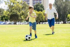 Young happy father and excited little 7 or 8 years old son playing together soccer football on city park garden running on grass k. Young happy father and Stock Image