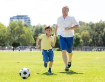 Young happy father and excited little 7 or 8 years old son playing together soccer football on city park garden running on grass k. Young happy father and Stock Photo