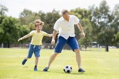 Young happy father and excited little 7 or 8 years old son playing together soccer football on city park garden running on grass k. Young happy father and royalty free stock images