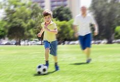 Young happy father and excited 7 or 8 years old son playing together soccer football on city park garden running on grass kicking royalty free stock photos