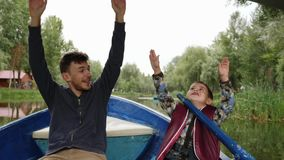 Young happy father and his little cute son floating on wooden boat under pedestrian bridge and raising their hands up. Happy famil. Y having fun on lake. Young stock video footage