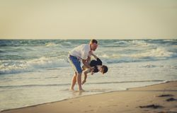 Young happy father holding in his arms little son playing on beach sand in front of sea waves Royalty Free Stock Photography