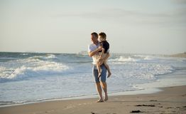 Young happy father holding in his arms little son walking on beach sand in front of sea waves Stock Image