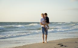 Young happy father holding in his arms little son walking on beach sand in front of sea waves Stock Photo